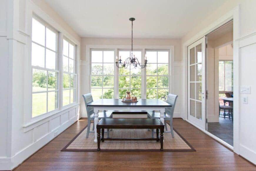 Classy dining room with wooden table and a pair of wooden bench and chairs brighten by a chandelier. This room has white walls and a window with a great view.