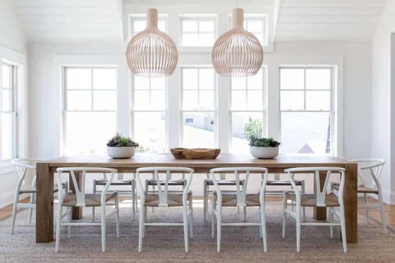 White dining room with wooden tables pair with white chairs on the rug. This room features a white ceiling and white walls with a window.