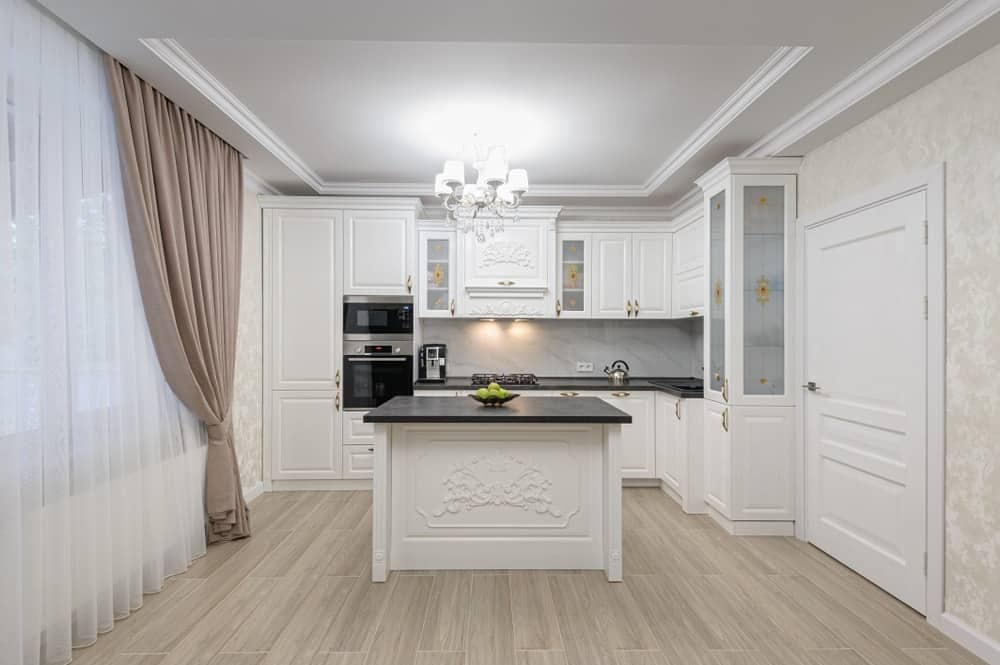 White kitchen with curtained windows, black appliances, and wood flooring.