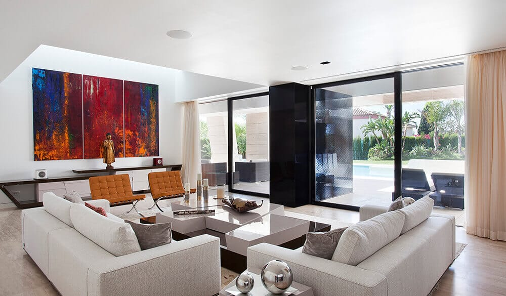 A modern house with a classy living room featuring a white wall with large wall decor. This room also features a classy sofa set and a large window with a great view outside.