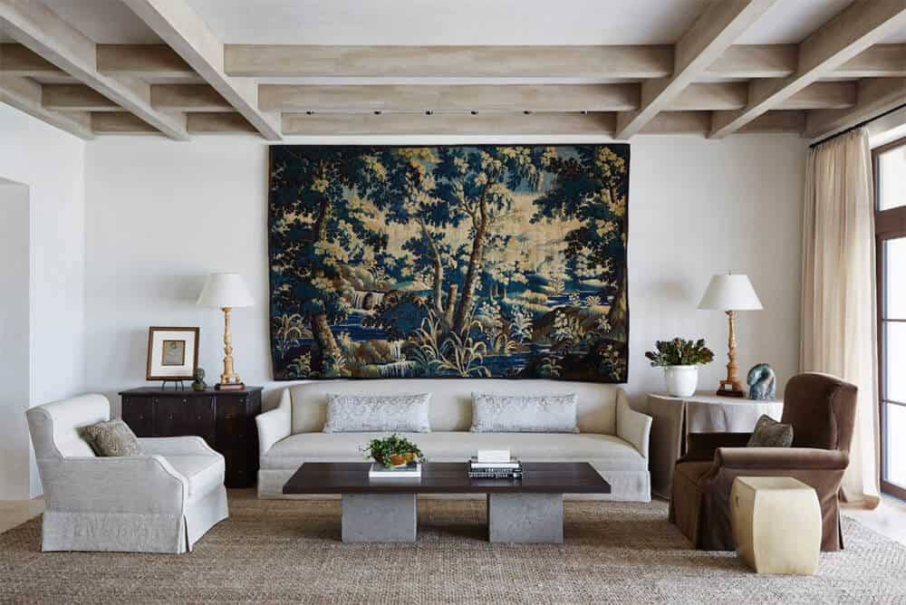 This formal living room highlighting a white wall with elegant decor and a gorgeous couch on the rug. The ceiling with exposed beams looks appealing as well.