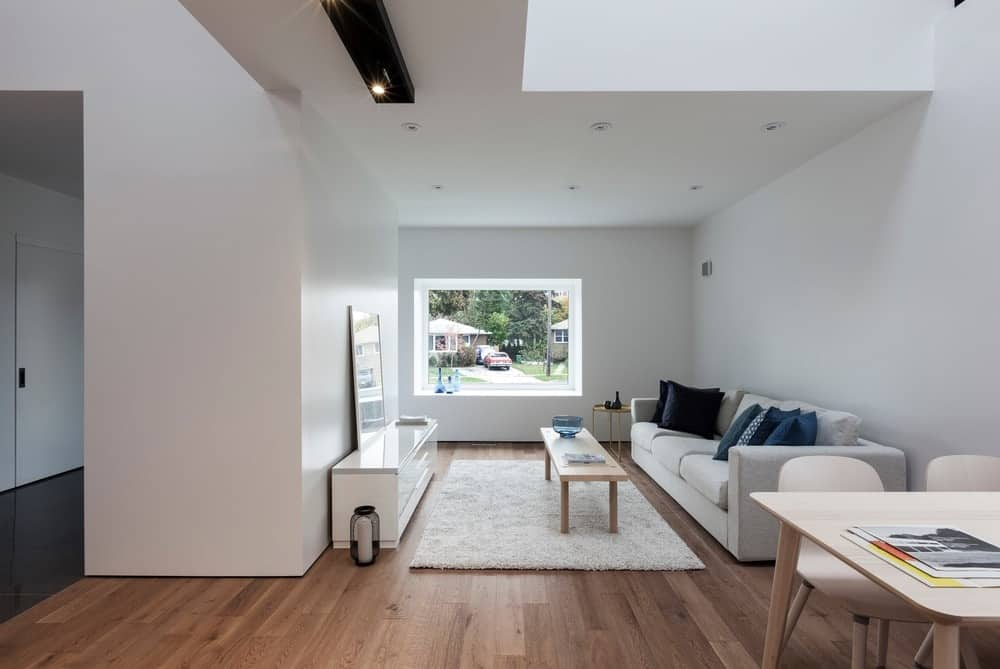 The small white living room features a classy sofa set on the top of hardwood flooring. There's a window with a view outside of the house.