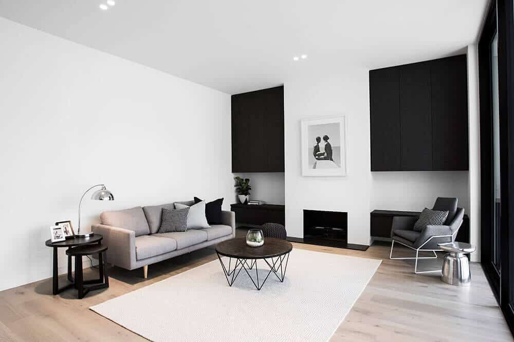 Modern white living room combined with black cabinet. This room features a wooden round table on the rug and a modern couch with a table lamp beside.