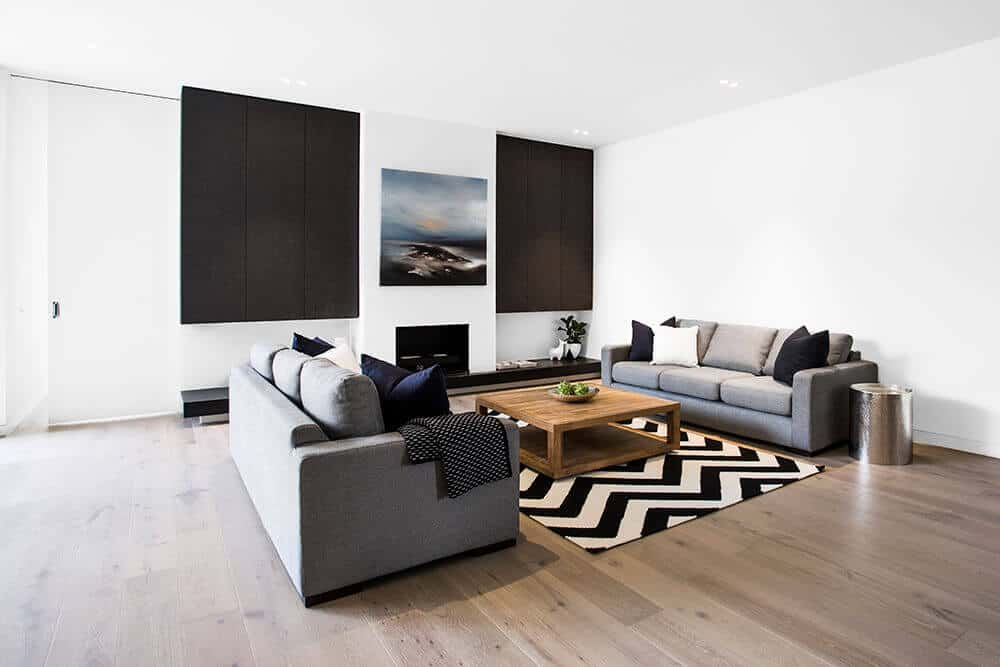 Classy living room design with a comfy couch and wooden table on the rug. This room also has white walls with decor and hardwood flooring.