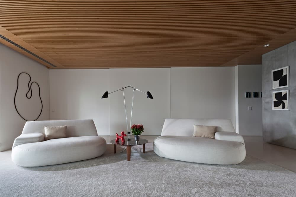 A large formal living room highlighting a huge white sofa set on the rug and a table lamp in the middle. The room also highlights white walls and attractive wall decors.