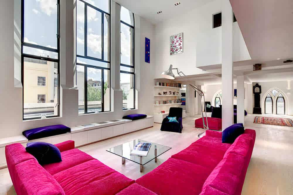 This living room featuring hardwood flooring a classy pink sofa set in front of the glass window. The room also features a stunning high ceiling.