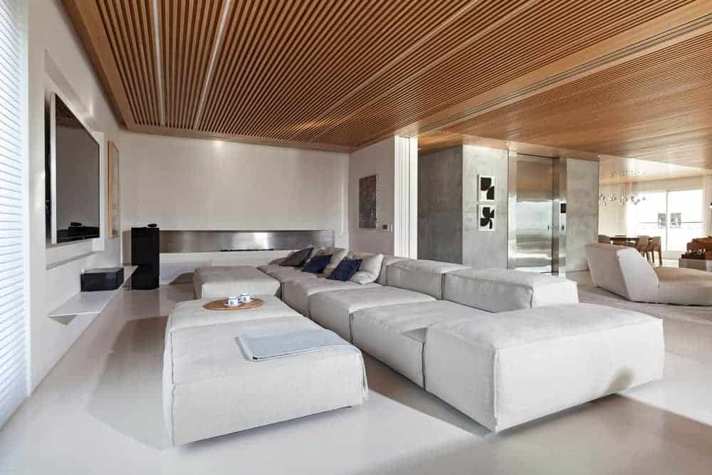 This front view of the living room featuring a white sofa set in front of the TV. This room white walls and wooden ceiling.
