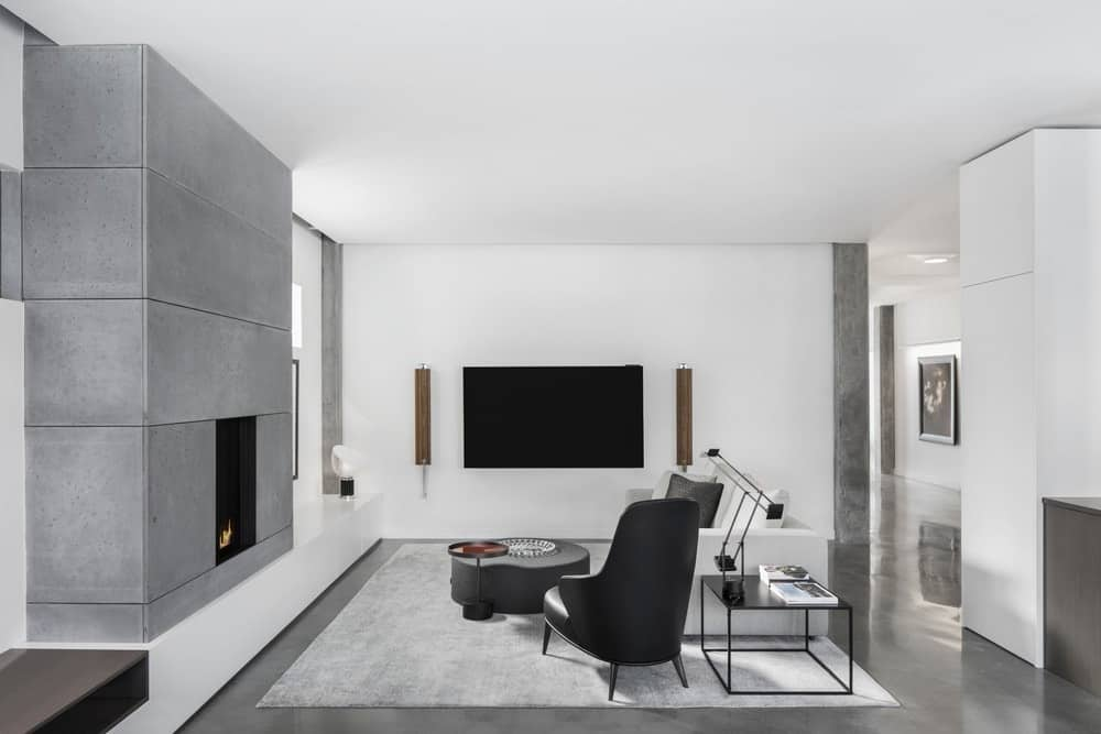 Modern living room featuring white walls and modern sofa set with a table on the rug. This room also has a TV on the wall and a great fireplace.