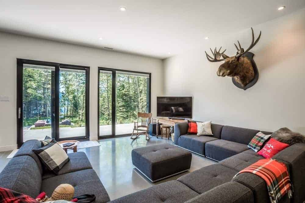 Contemporary living room highlighting a classy U-shape grey sofa set ringed by the white ceiling and white walls with reindeer head design.