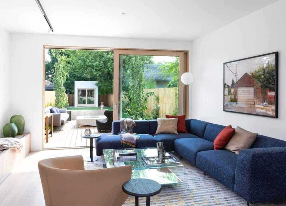 Small living room with blue L-shaped sofa set and glass table on the rug. This room has a sliding glass door leading to the terrace.