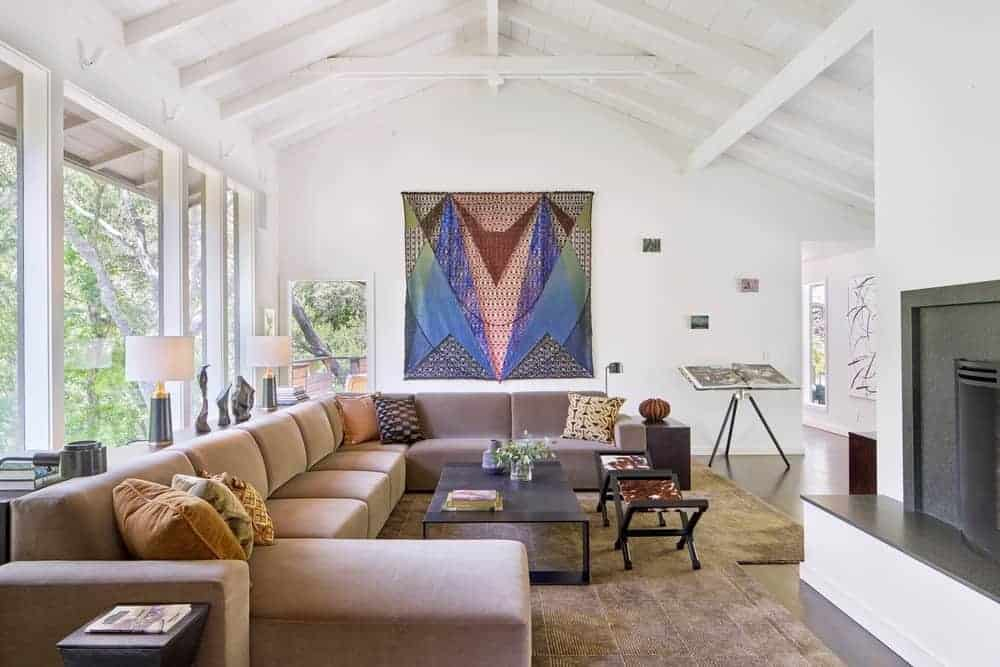 This formal living space promoting a great design of the sofa set on the top of a stylish rug under the arched ceiling with beams.