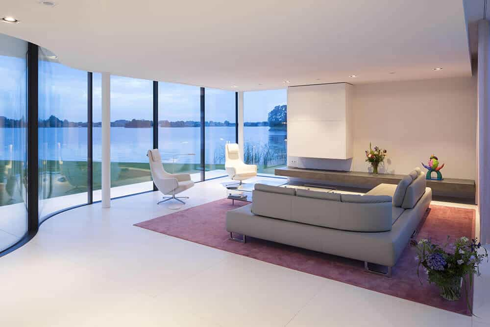 This modern living room looks so attractive with its comfortable couch set and white wall and floors. This room has glass wall with an impressive view outside.
