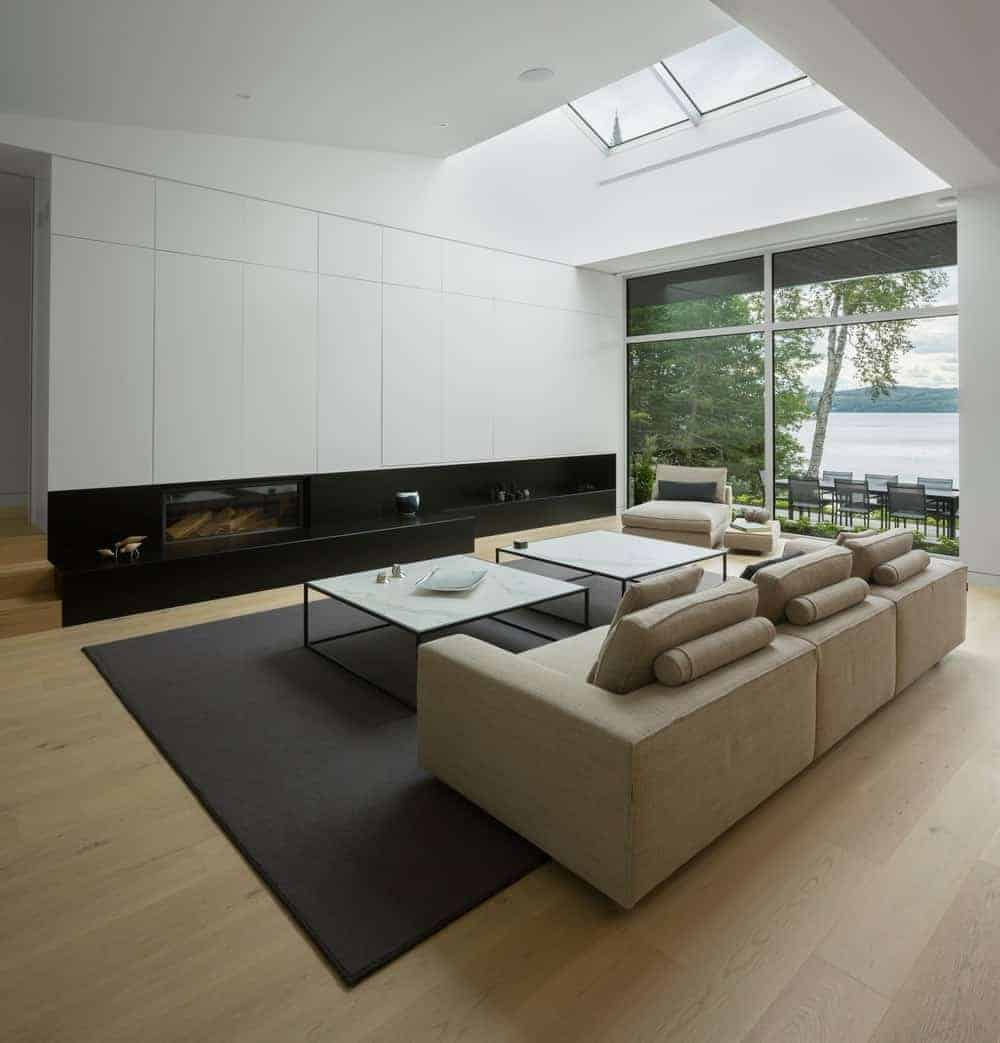 This living room looks perfect with its hardwood flooring and brown sofa set with a pair of a square table on the rug. This room has glass wall with a view of the backyard.