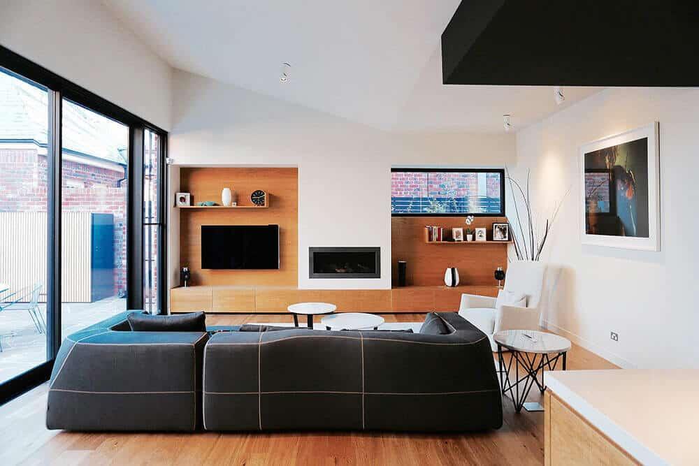 A gorgeous living room with a classic black sofa set on the hardwood flooring surrounded with white walls and ceiling.