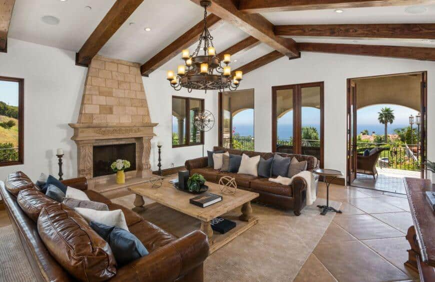 A Mediterranean home highlighting a living room with an classic sofa set and wooden table on the carpet. This room also has a classy fireplace lighted by a stunning chandelier.