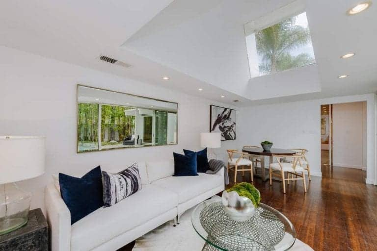 Small white living space features classy hardwood flooring and white vaulted ceiling. This room also has a dining space with a round table set and wooden chairs.