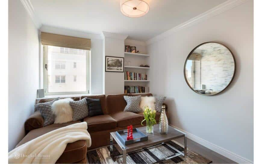 Small living room featuring an L-shaped brown sofa set. This room also has white walls with a circular mirror and bookshelf.