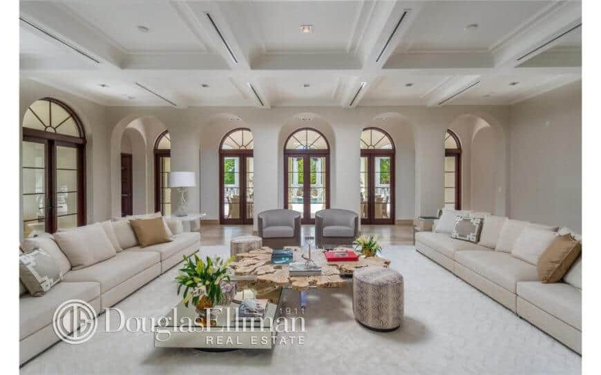 Contemporary home offering a huge formal living room with an exquisite couch set on a white floor covering. The dazzling roof with its lighting looks amuses as well.