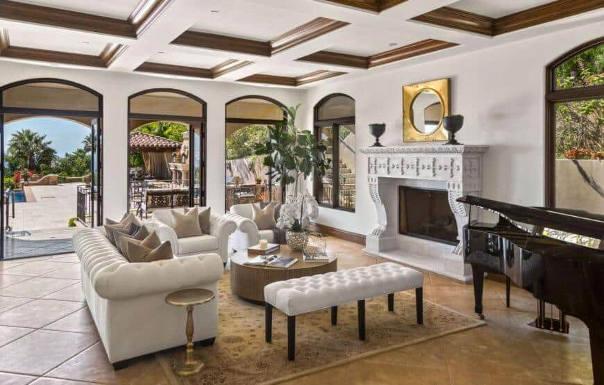The elegant mansion features a formal living space with a white sofa set and wooden table on the carpet. This room also features an elegant black piano.