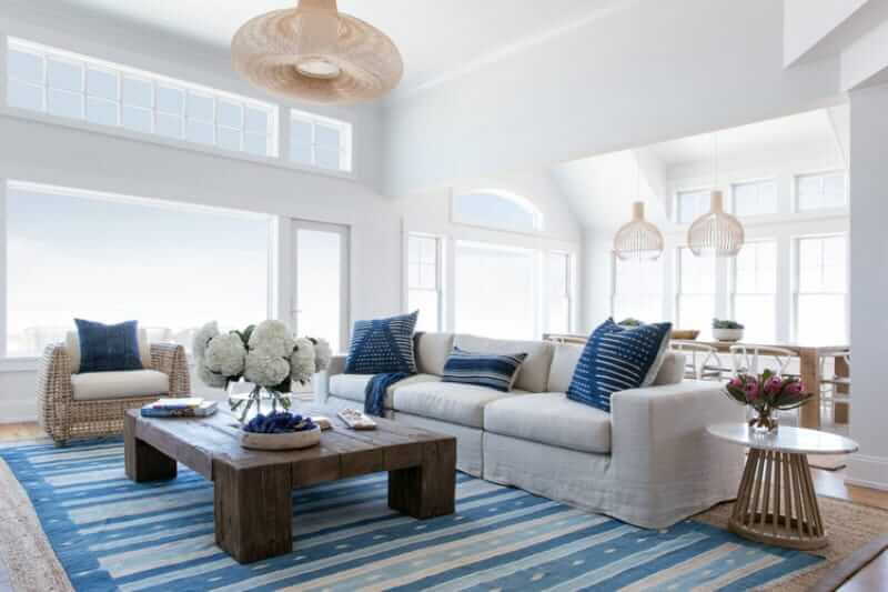 Bright living room with a stylish sofa set design with a wooden table on the rug. This room has huge window and a great overlooking view.