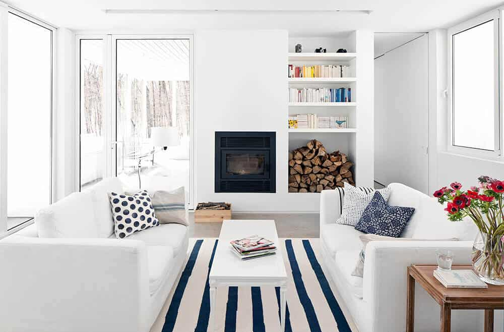 Bright living space with white walls and ceiling coordinated by white sofa set and white rectangular table on top of the carpet. This room also has a fireplace.
