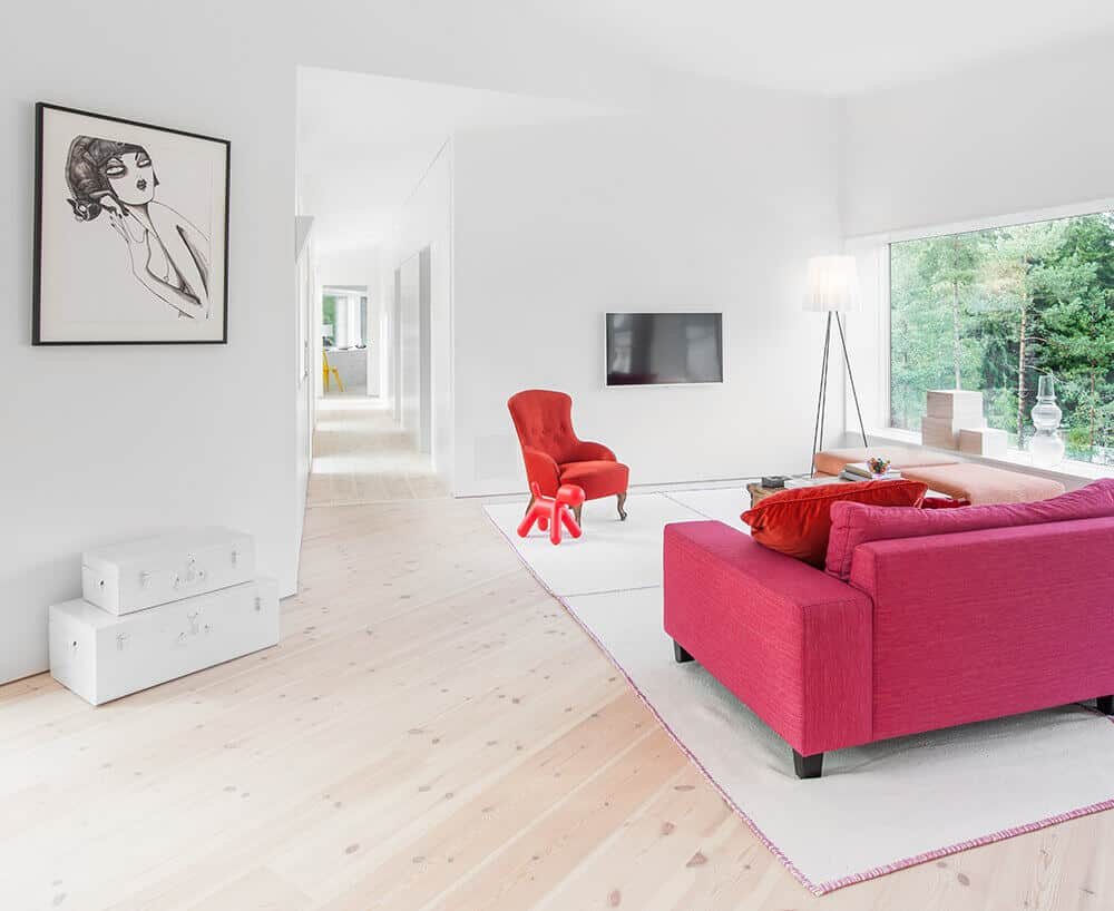 White living room with an attractive red sofa set on the carpet and also has a TV on the wall. This room has a glass wall with a great view.