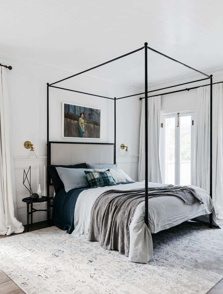 A direct shot at this master bedroom's sleek bed set with a nice painting and edgy bed frame on the carpet topped on the room's hardwood flooring.