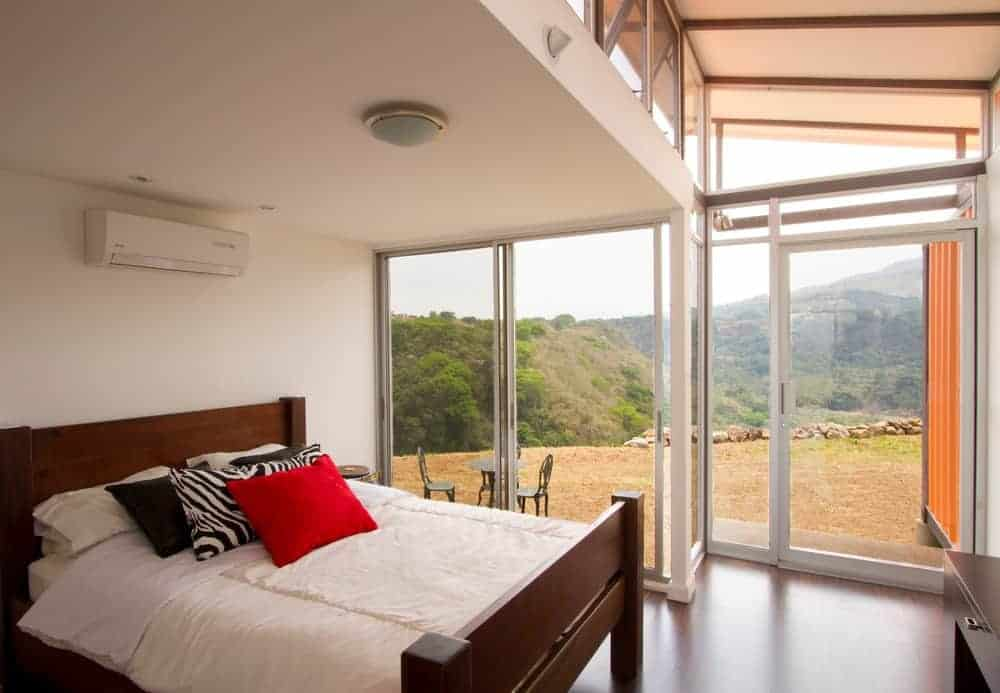 This modern master bedroom has white walls alongside a flush mount lighting. It has glass walls showing a stunning scene outside.