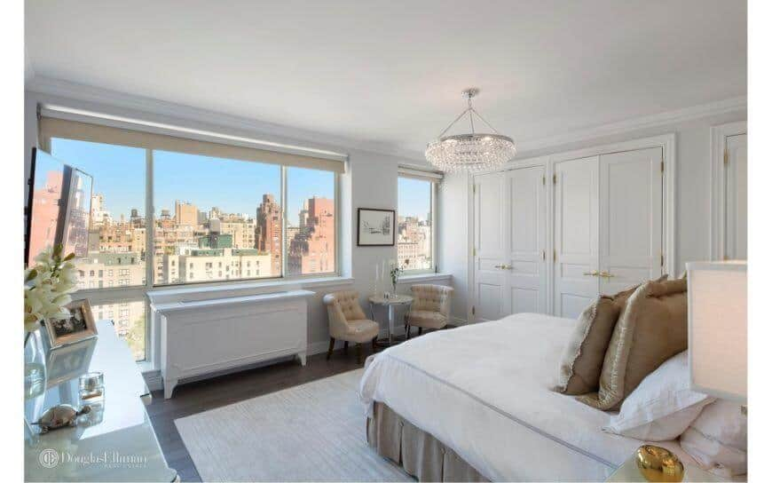 This master bedroom highlights hardwood flooring covered by an area carpet. It has a large windows with a sitting area nearby and a beautiful view outside. The room is lit by an extravagant light fixture.