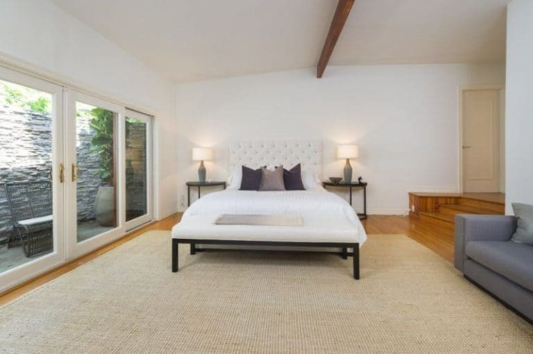 This master bedroom boasts a huge mat covering the hardwood flooring. It has a gray couch on the side. The bed is lighted by two table lights on the sides.