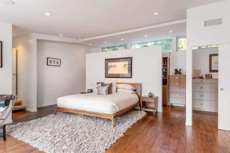 The master bedroom looks gorgeous with dispersed recessed lights on the white ceiling. The hardwood flooring combined altogether with white walls and the carpet matches with the bed perfectly.