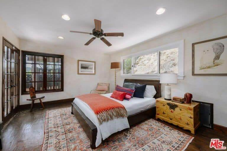 This master bedroom has a lot of wooden touch from the wooden-framed window to the hardwood flooring covered by a carpet with an Aztec design. It has a wooden chair, wooden side table, and a wooden bed frame.