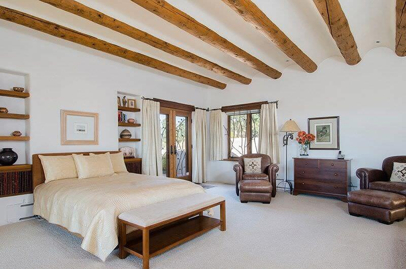 A carpeted white bedroom that highlights roof bends with wood beams promoting acoustic and stylish sense.