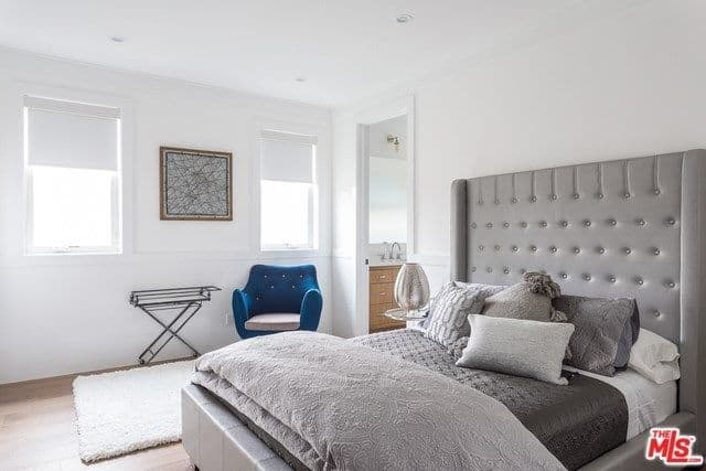 This master bedroom has a monochromatic gray bed design surrounded by white walls and ceiling and has a cute little blue side chair that stands out.