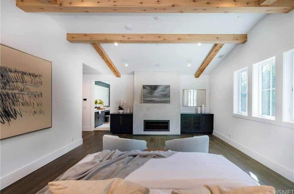 This master bedroom has its own washroom. The bedroom highlights white walls with wall decor and a white ceiling with exposed beams.