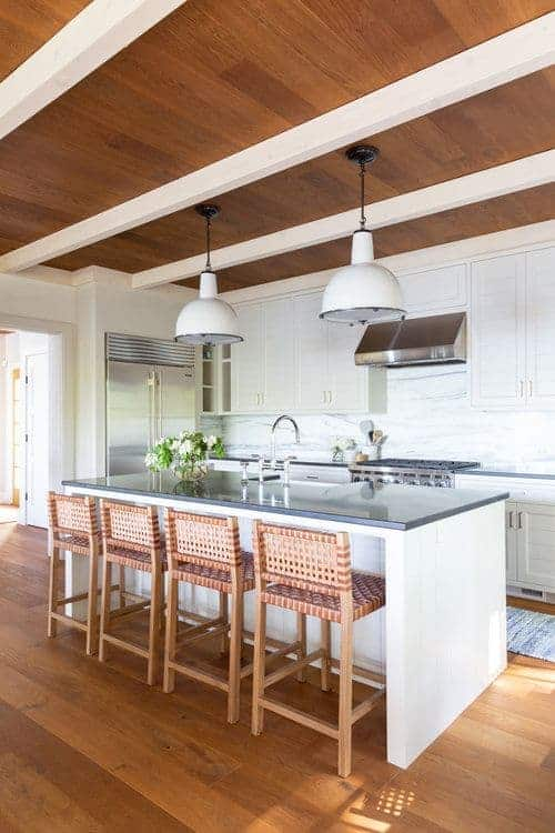 For a shabby chic style, this kitchen has a white island with a grey countertop. The woven four-legs chairs match the wooden flooring just right, while the white splashback and pantry match the inverted bowl hanging lights.