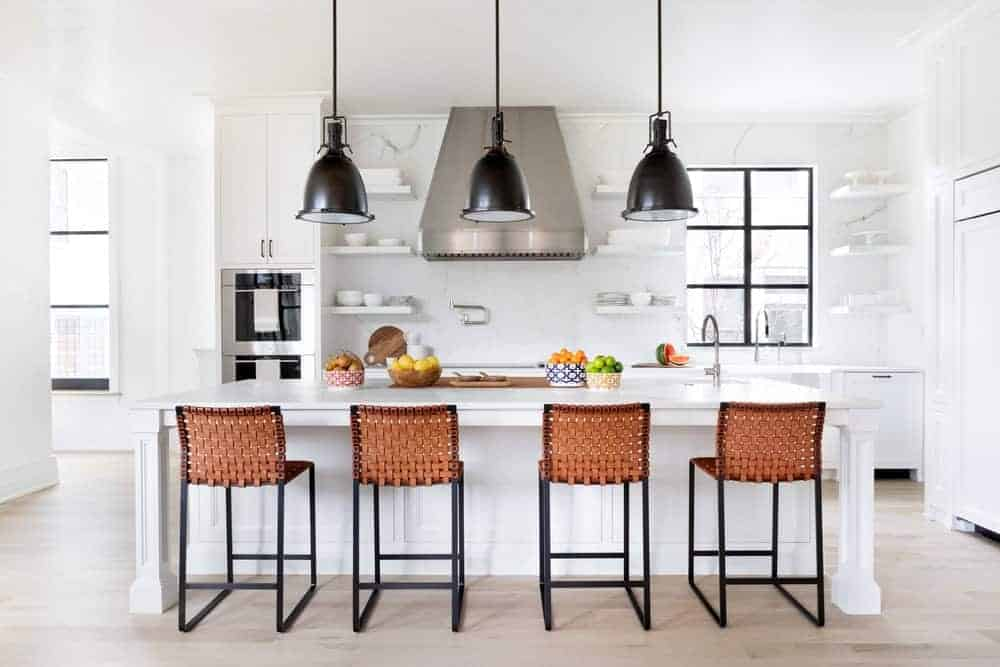 A simple Mediterranean kitchen could be achieved perfectly with white walls, shelves, and an island right in the middle of the kitchen. The woven four-legs bar stools complement this style, along with the black pendant lights.