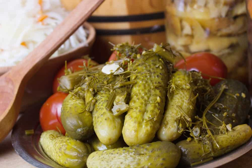 A yummy plate of pickles with herbs and tomatoes.