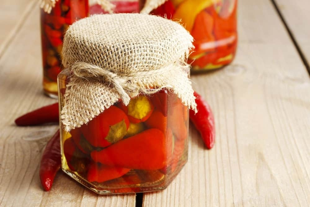 A jar of pickled red peppers on a wooden surface.