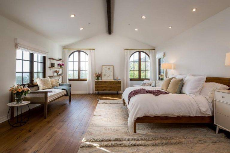 A comfortable master bedroom featuring hardwood flooring cover by a large carpet with white walls and ceiling.