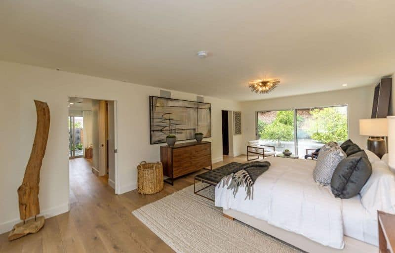 This master bedroom featuring hardwood flooring and a king-sized bed. The room also offers a comfy seating area with a large glass window and a great view outside.