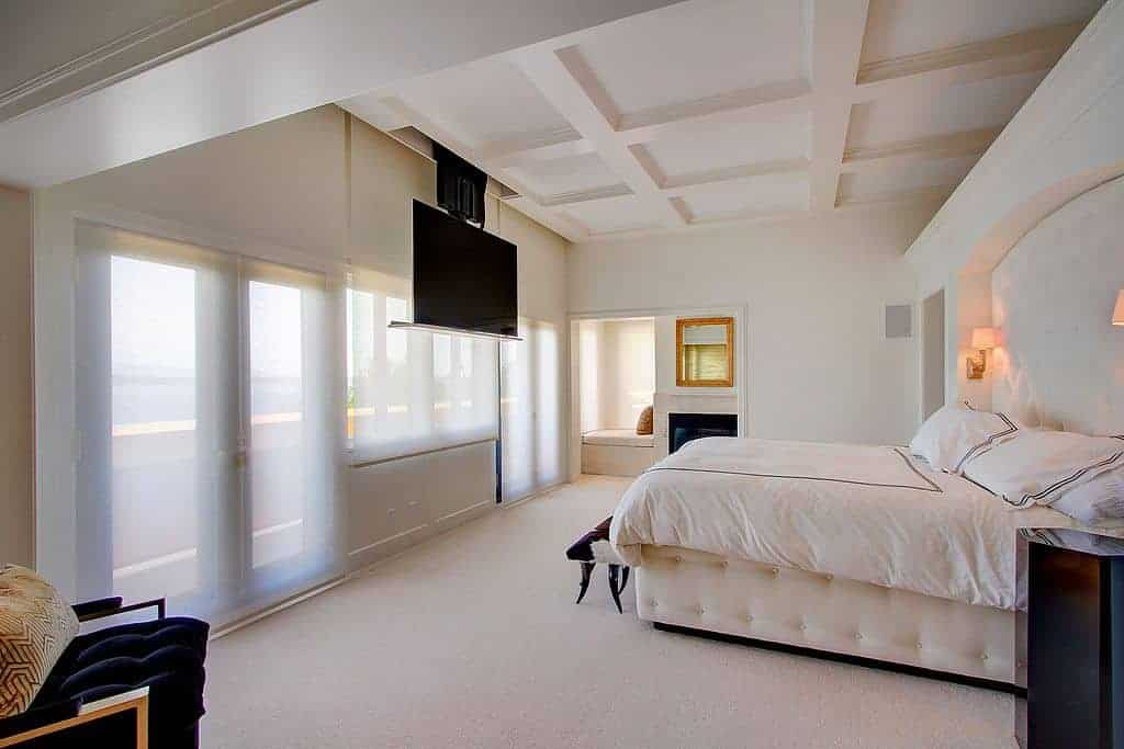 This white master bedroom features a large widescreen TV hanging from the ceiling in front of the large bed set lighted by two built-in lamps beside. The room offers a modern chair on the side.