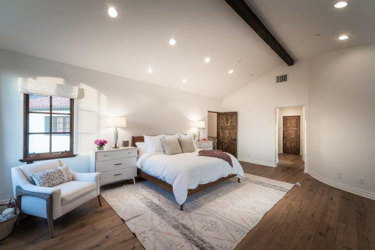 A spacious master bedroom featuring hardwood flooring topped by a large area rug along with white walls and a vaulted ceiling with an exposed beam.