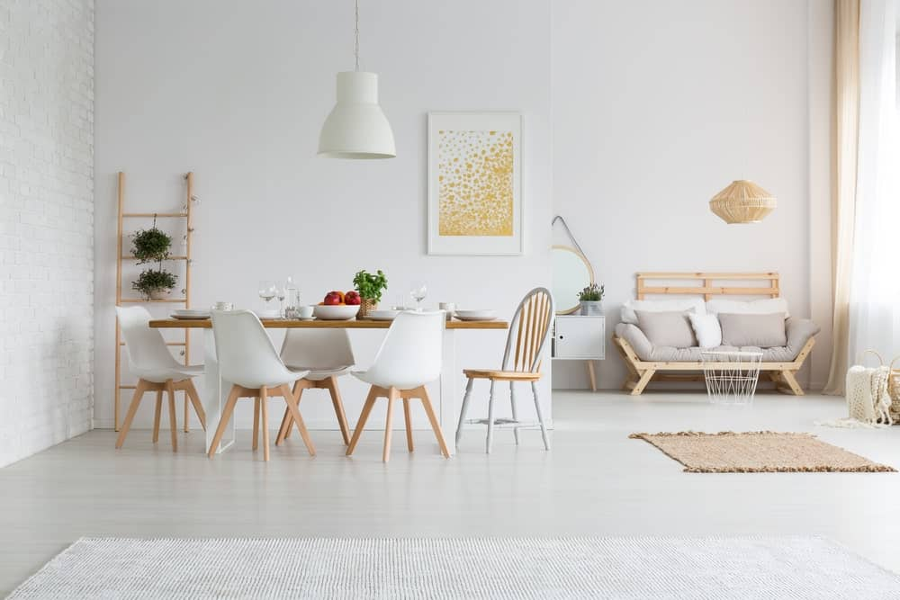 Stylish white studio apartment with dining room and living room. It also has wooden tables with modern chairs.