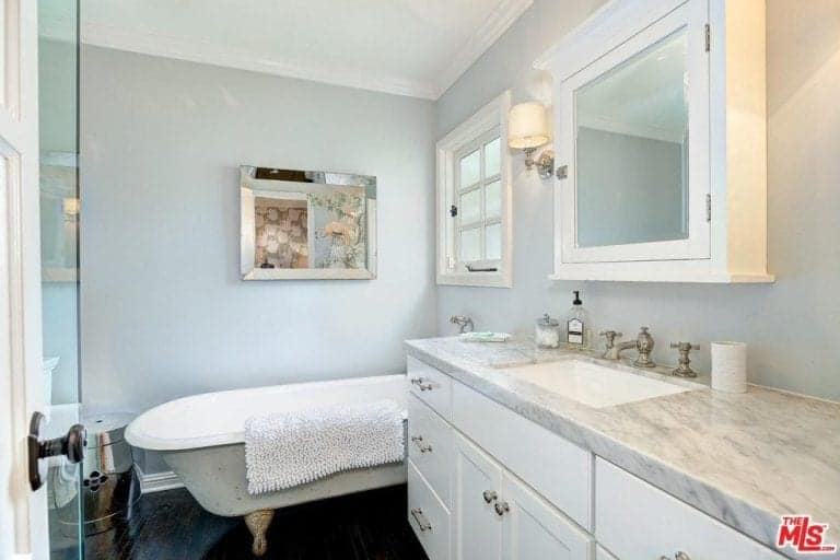 Modern primary bathroom with fancy clawfoot tub and a white sink vanity topped with a medicine cabinet and classic wall sconce.