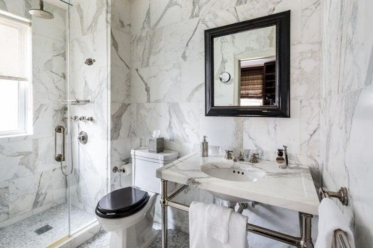The marbled bathroom offers a drop-in bathtub and mirrored sink vanity topped with a quartz counter and paired with a glam mirror lighted by a vintage wall sconce.