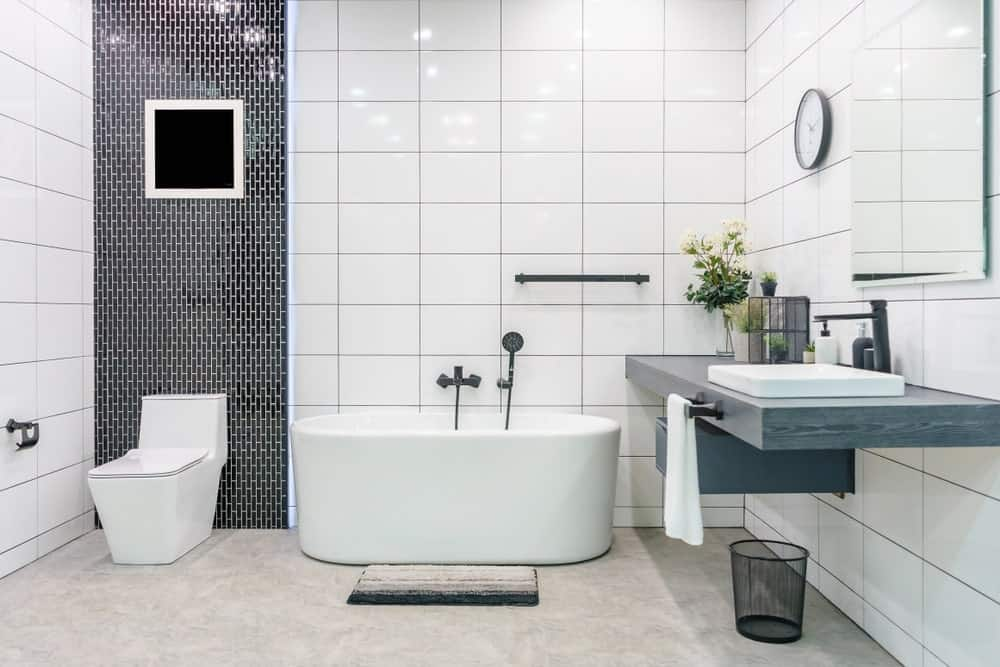 Modern bathroom interior with minimalistic shower and lighting, white toilet, sink, and bathtub. It also has a marble countertops that match the marble flooring.
