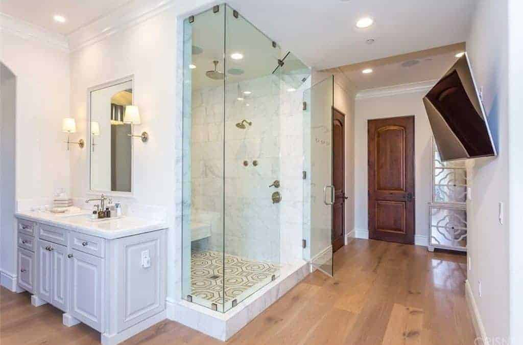 This primary bathroom contrasted with a white wood sink vanity that sits beside the walk-in shower enclosed in glass. It has a TV hanging on the wall in front of the walk-in shower.