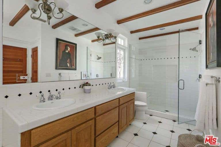 An enchanting portrait is reflecting in the frameless mirror mounted with vintage sconces in this primary bathroom with wood beam ceiling and white tiled flooring accented by the black diamond pattern.