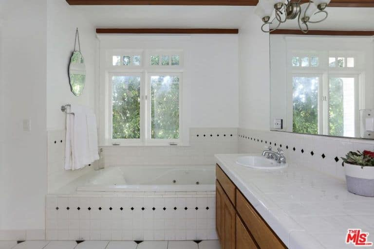 Small primary bathroom highlighting a drop in the bathtub next to the wooden vanity and underneath a white framed window bringing natural light in.